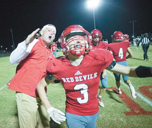 Prague assistant coach Tony Willoughby celebrates with defensive back Aiden Auld in the waning seconds of the Red Devils' win over Crossings Christian Friday night. Auld intercepted a pass in the end zone to clinch the victory. Photo/Brian Blansett